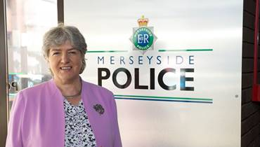 Jane standing in front of a Merseyside Police sign